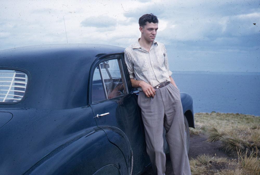 Man leaning on car near the beach